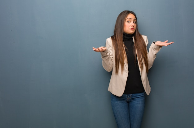 Giovane donna di affari che dubita e che scrolla le spalle le spalle