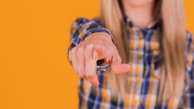 Giovane donna di affari che indica la sua barretta verso la macchina fotografica contro priorità bassa arancione