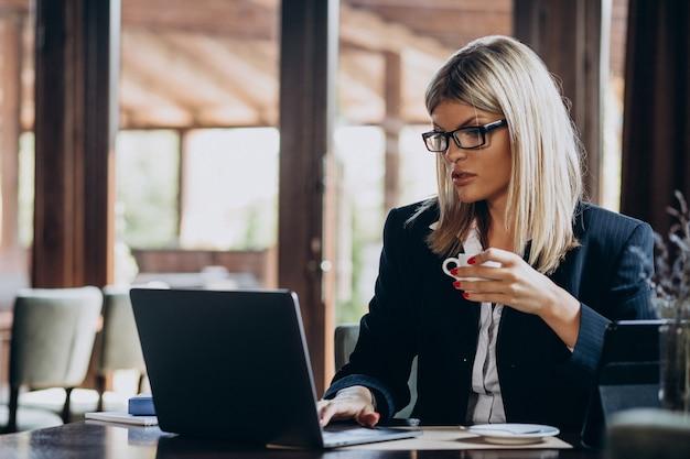 Giovane donna di affari che lavora al computer in un caffè