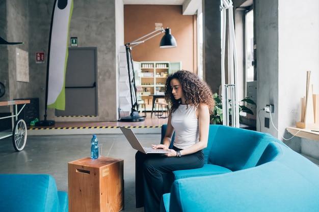 Giovane donna di affari che lavora e che si siede con il computer portatile in ufficio moderno