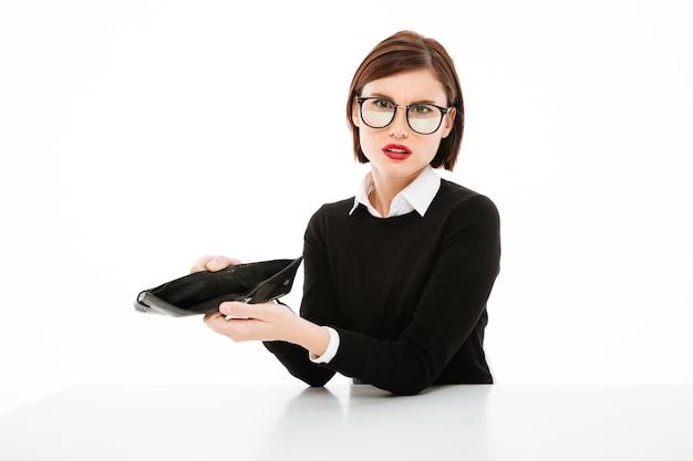 Giovane donna di affari che mostra portafoglio vuoto
