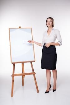 Giovane donna di affari che mostra qualcosa su bianco
