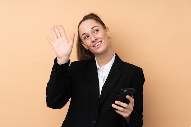 Giovane donna di affari che per mezzo del telefono cellulare sopra la parete isolata che saluta con la mano con l'espressione felice