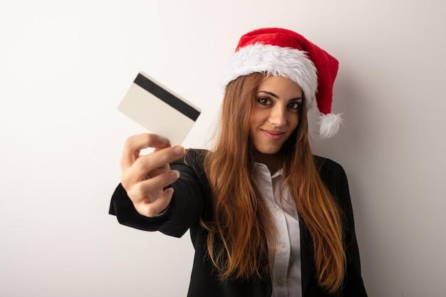 Giovane donna di affari che porta il cappello della santa che celebra giorno di natale