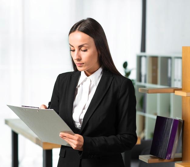 Giovane donna di affari che scrive sulla lavagna per appunti con la penna