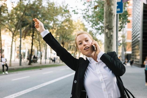 Giovane donna di affari che solleva mano per fermare l'automobile sulla strada di città