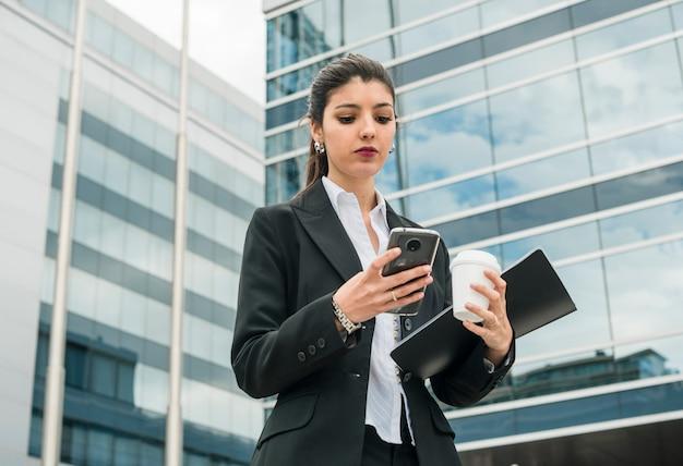 Giovane donna di affari che sta davanti alla costruzione che esamina telefono cellulare che tiene la tazza di caffè asportabile a disposizione
