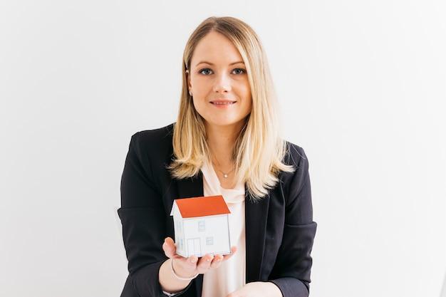 Giovane donna di affari che tiene il modello di casa in miniatura su sfondo bianco