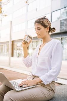 Giovane donna di affari che tiene la tazza di caffè asportabile che scrive sul computer portatile