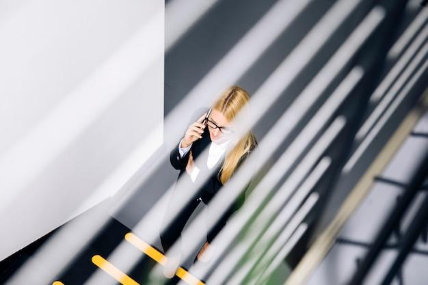 Giovane donna di affari che utilizza telefono cellulare mentre scala le scale in ufficio