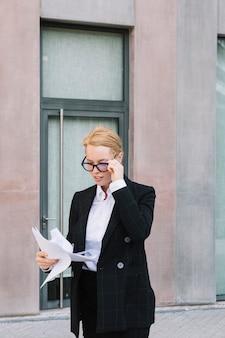 Giovane donna di affari con la mano sugli occhiali che esaminano i documenti