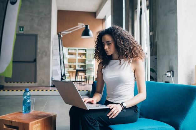 Giovane donna di affari del brunette che lavora e che si siede con il computer portatile in ufficio moderno