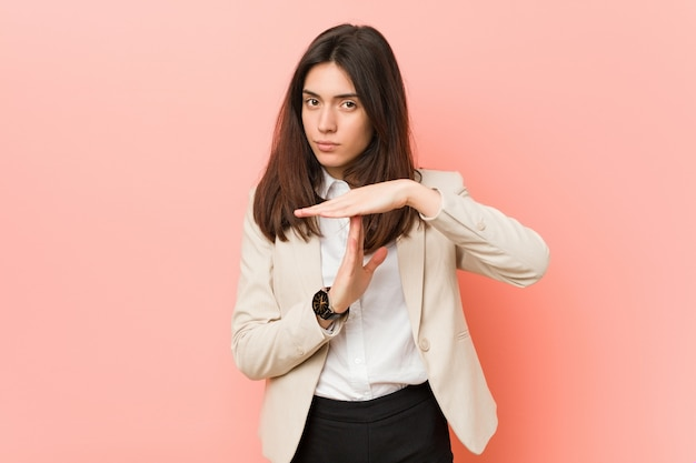 Giovane donna di affari del brunette che mostra un gesto di timeout