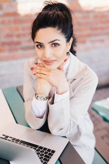 Giovane donna di affari del brunette con gli occhi affascinanti, mani delicate con l'uso rosso del manicure