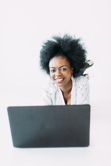 Giovane donna di affari dell'afroamericano che per mezzo del computer portatile, mentre trovandosi sul pavimento, isolato
