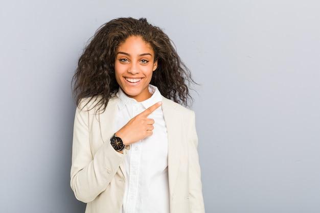 Giovane donna di affari dell'afroamericano che sorride e che indica da parte, mostrando qualcosa nello spazio.