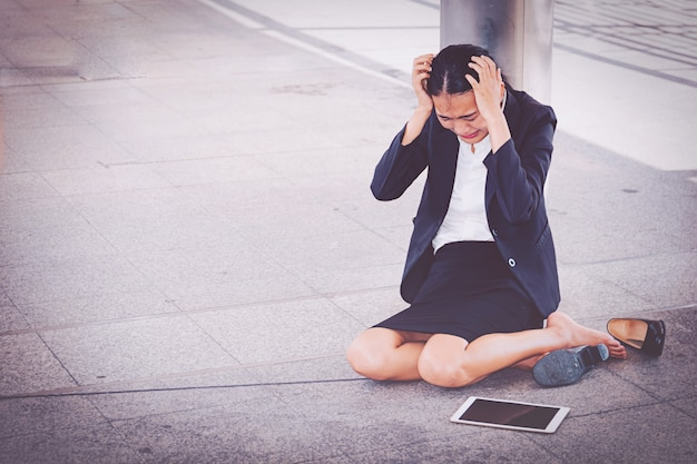 Giovane donna di affari depressa che si siede sul pavimento