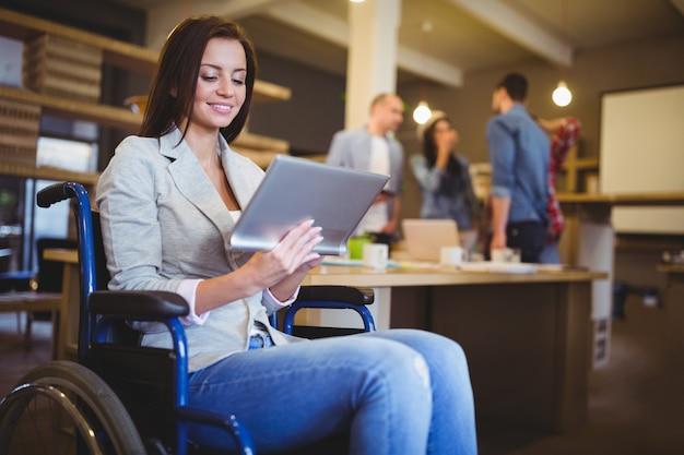 Giovane donna di affari disabile che per mezzo della compressa digitale