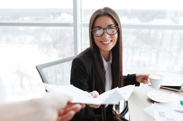 Giovane donna di affari felice che si siede e che riceve i documenti in ufficio