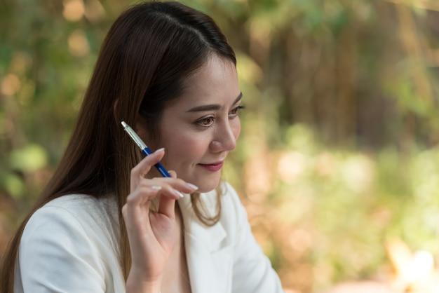 Giovane donna di affari felice con la soluzione di pensiero della penna.