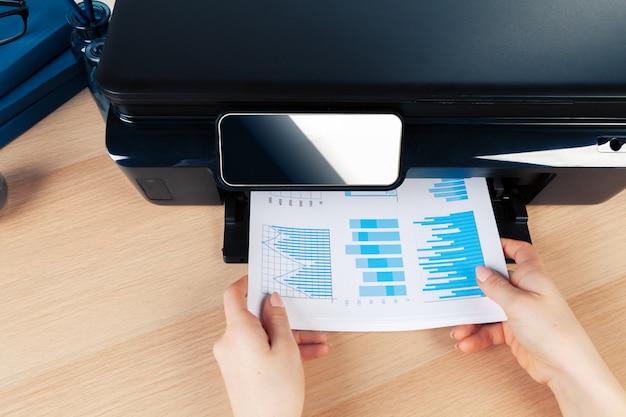 Giovane donna di affari irriconoscibile che fa le copie sulla macchina della fotocopiatrice all'ufficio