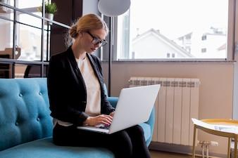 Giovane donna di affari moderna che utilizza computer portatile nell'ufficio