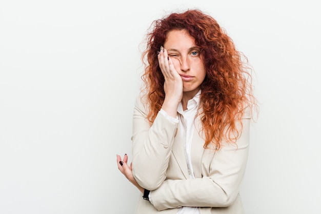 Giovane donna di affari naturale rossa su sfondo bianco che è annoiato, affaticato e ha bisogno di una giornata di relax.