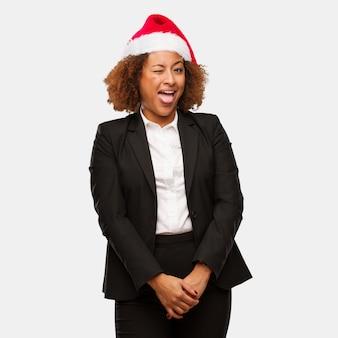 Giovane donna di affari nera che indossa un cappello di babbo natale divertente e divertente che mostra la lingua