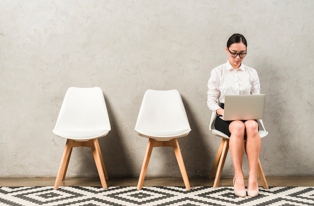 Giovane donna di affari seria asiatica che si siede sulla sedia che scrive sopra il computer portatile