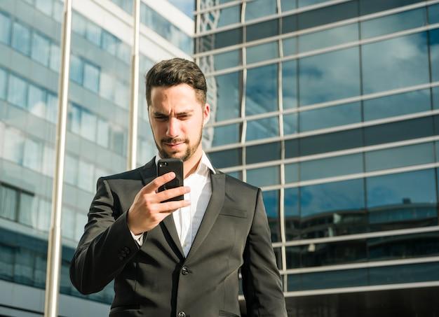 Giovane donna di affari seria che esamina telefono cellulare che sta nella parte anteriore dell'edificio corporativo