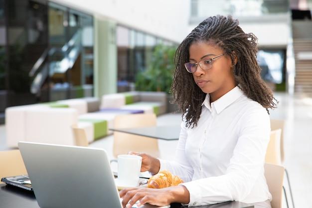 Giovane donna di affari seria che mangia prima colazione