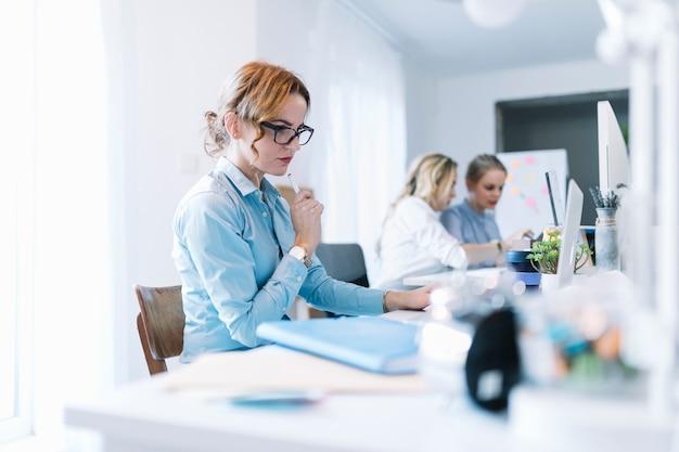 Giovane donna di affari sicura che lavora al computer portatile in ufficio