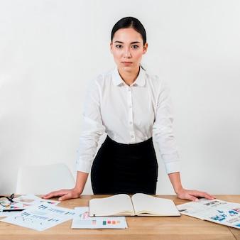 Giovane donna di affari sicura che si leva in piedi alla scrivania contro la parete bianca