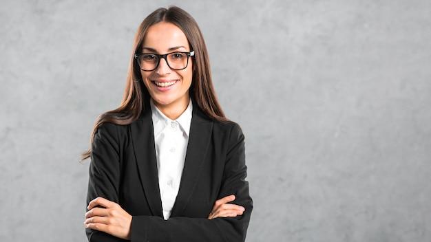 Giovane donna di affari sicura che sta contro la parete grigia