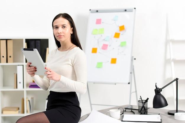 Giovane donna di affari sicura che tiene compressa digitale a disposizione che si siede sulla tavola nel luogo di lavoro