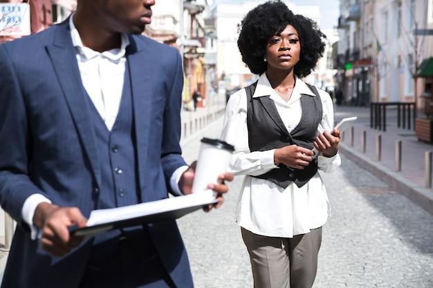 Giovane donna di affari sicura che tiene compressa digitale che cammina con il suo collega nella città