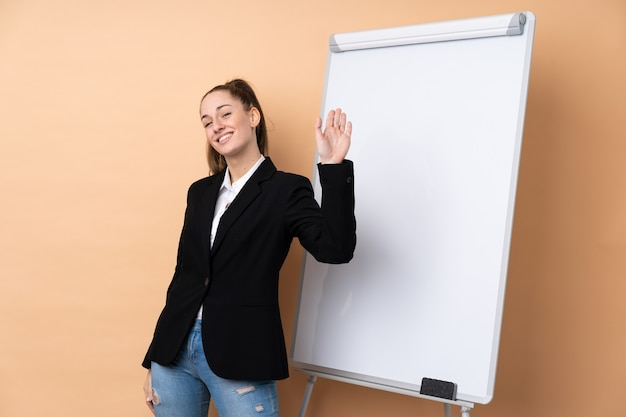 Giovane donna di affari sopra la parete isolata che dà una presentazione sul bordo bianco e che saluta con la mano