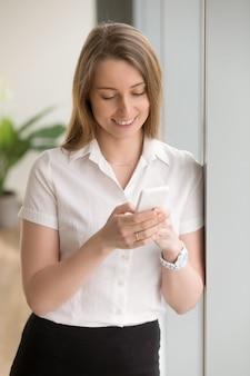 Giovane donna di affari sorridente che controlla telefono, messaggio mandante un sms, facendo uso delle applicazioni aziendali