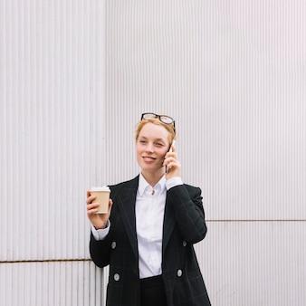 Giovane donna di affari sorridente che parla sul telefono cellulare che tiene la tazza di caffè asportabile