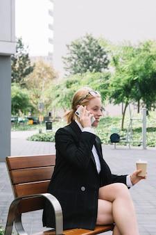 Giovane donna di affari sorridente che si siede sul banco che tiene la tazza di caffè asportabile che parla sul telefono cellulare