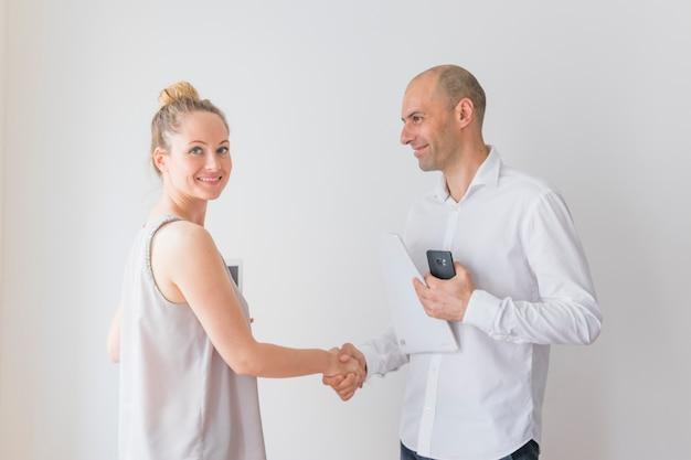 Giovane donna di affari sorridente che stringe mano con la carta della tenuta dell'uomo d'affari e cellulare