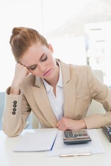 Giovane donna di affari stanca che riposa alla scrivania