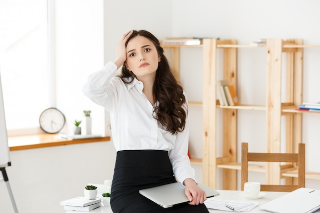 Giovane donna di affari stanca che soffre da molto tempo che si siede allo scrittorio del computer in ufficio
