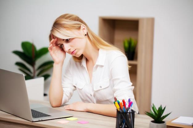 Giovane donna di affari stanca esaurita nel luogo di lavoro nel suo ufficio