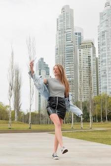Giovane donna di angolo basso che prende selfie