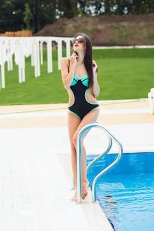 Giovane donna di bella forma fisica in costume da bagno sulla località di soggiorno tropicale