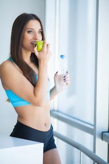 Giovane donna di bella misura che tiene una bottiglia di acqua e una mela verde