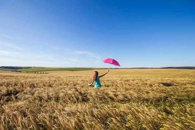 Giovane donna di bellezza all'aperto che gode della natura. bella ragazza modello adolescente in abito blu con ombrello rosso sul campo di grano alla luce del sole.