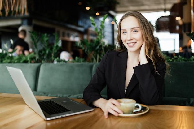 Giovane donna di bellezza che lavora al computer portatile nella caffetteria