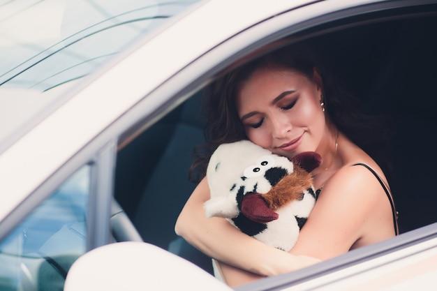 Giovane donna di bellezza e piccolo peluche in vestiti in auto.